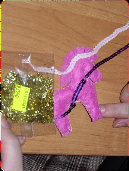 Поскольку мулине, которым обшита фигурка, светлое, для украшения самой лошадки я выбрала нежно - розовые пайетки и золотистые цветочки